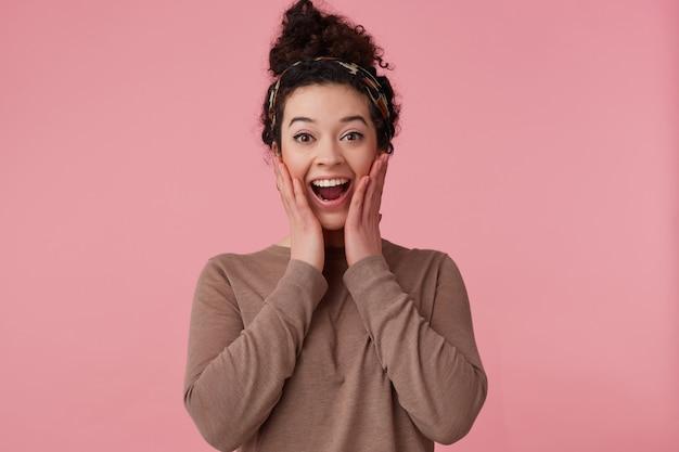 Ritratto di ragazza attraente e stupita con panino scuro dei capelli ricci. indossare cerchietto e maglione marrone. ha il trucco. toccando il viso sorpreso