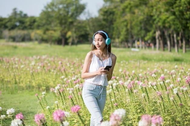 Il ritratto di una donna asiatica attraente ascolta musica online sullo smartphone e cammina per godersi il giardino di fiori rosa primaverili al mattino. stile di vita all'aperto. rinfresco della ragazza castana nel parco di estate.