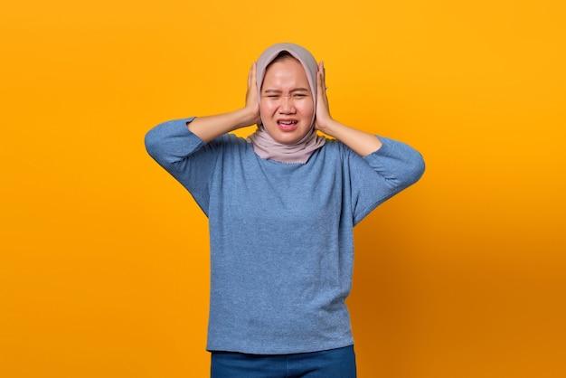 Ritratto di una donna asiatica attraente che sembra stressata e preoccupata per lo sfondo giallo