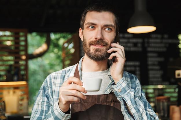Ritratto di un attraente barista che indossa un grembiule che beve caffè e parla al cellulare in un caffè di strada o in un caffè all'aperto