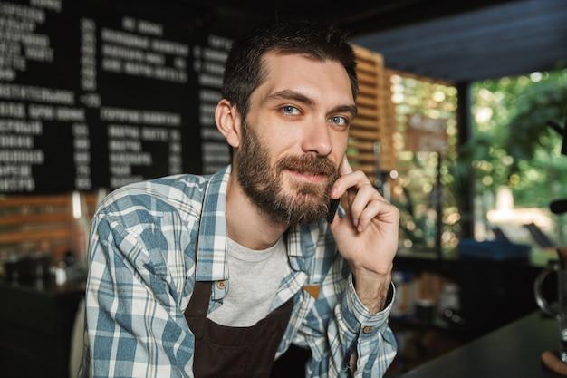 Ritratto di un attraente barista che indossa un grembiule che sorride e parla al cellulare in un caffè di strada o in un caffè all'aperto