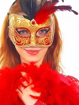 Ritratto di attraente bella giovane donna che indossa la maschera di carnevale d'oro