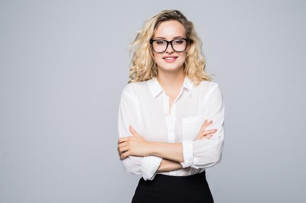 Ritratto di attraente bionda imprenditrice in bicchieri con le braccia incrociate isolato sul muro bianco