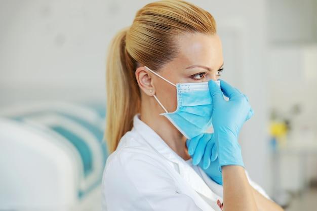 Ritratto di assistente di laboratorio bionda attraente con guanti di gomma in piedi in ospedale e mettendo su maschera facciale sterile.