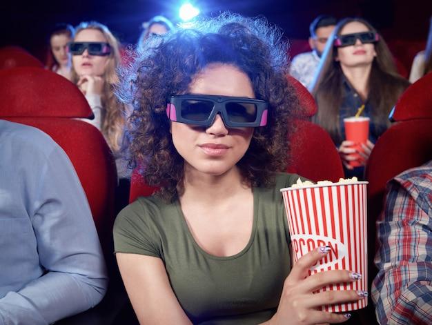 Ritratto di attraente bruna, sorridente e in posa durante il film nella sala cinema. ragazza graziosa che mangia popcorn e che guarda commedia interessante divertente. concetto di intrattenimento.