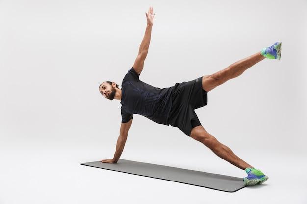 Ritratto di uno sportivo brunetta attraente in tuta sportiva che fa allenamento sul tappetino yoga isolato su bianco