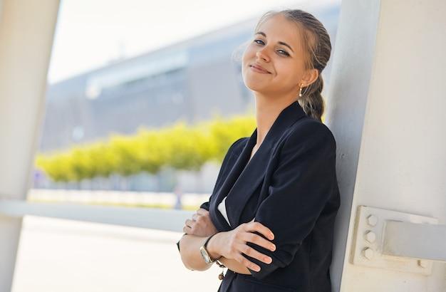 Ritratto di una donna d'affari attraente in piedi davanti a finestre un edificio per uffici