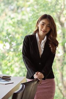 Ritratto di donna d'affari attraente in piedi accanto al tavolo della riunione nella sala riunioni