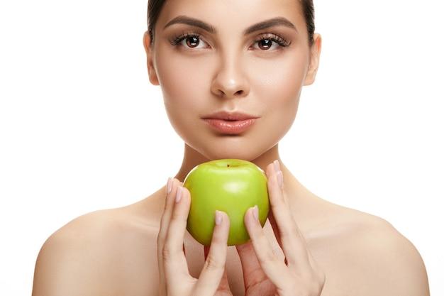 Ritratto di sorridere caucasico attraente che tiene una donna della mela verde isolata su bianco