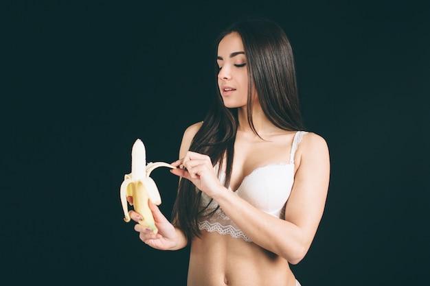 Ritratto della donna sorridente caucasica attraente che mangia banana.