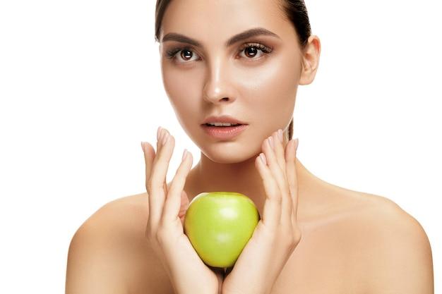 Il ritratto della donna sorridente caucasica attraente isolata sulla parete bianca con i frutti della mela verde. la bellezza, la cura, la pelle, il trattamento, la salute, le terme, i cosmetici