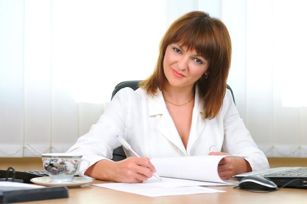 Ritratto di donna bruna bianca caucasica attraente con penna e cartella con i documenti. impiegato. imprenditrice.
