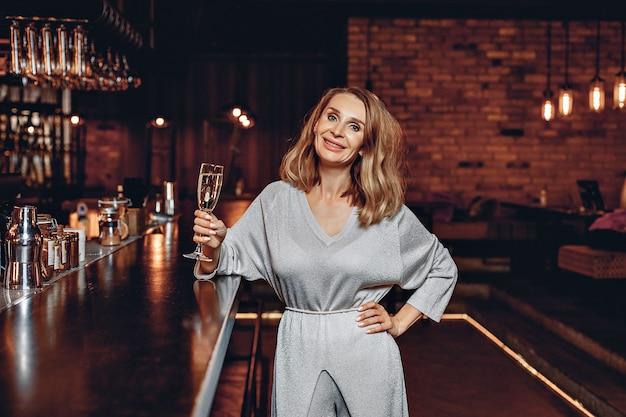 Ritratto di una donna affascinante e attraente in un bellissimo vestito d'argento in piedi vicino al bar, con in mano un bicchiere di champagne