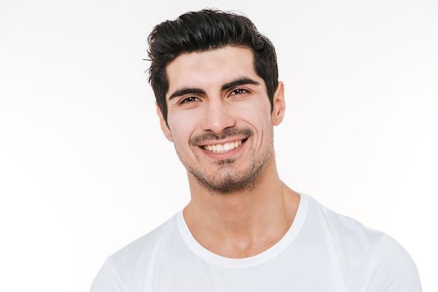 Ritratto dell'uomo allegro attraente che controlla la parete bianca.