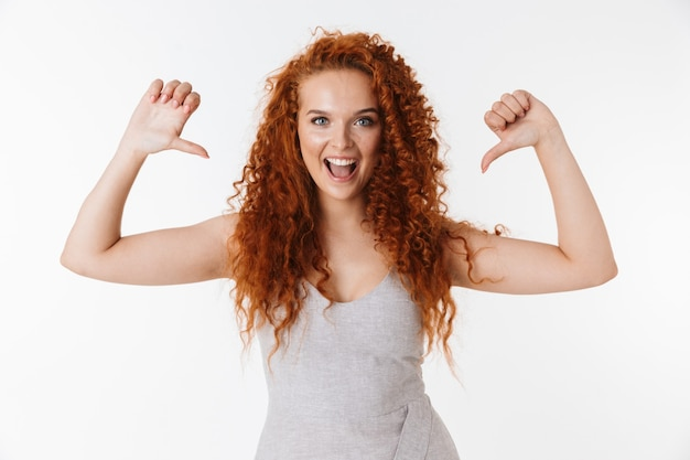 Ritratto di un'attraente giovane donna allegra con lunghi capelli rossi ricci in piedi isolata, indicando se stessa