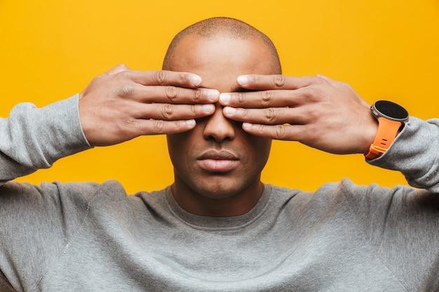Ritratto di un giovane africano attraente e sicuro di sé che sta sopra il muro giallo, copre gli occhi