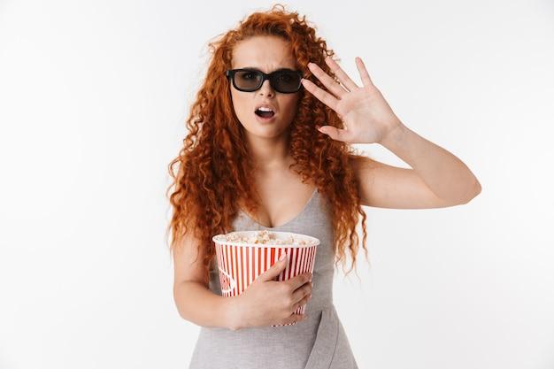 Ritratto di un'attraente giovane donna confusa con lunghi capelli rossi ricci in piedi isolata, guardando un film e mangiando popcorn