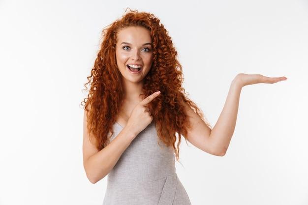 Ritratto di un'attraente giovane donna eccitata con lunghi capelli rossi ricci in piedi isolata, presentando lo spazio della copia, indicando