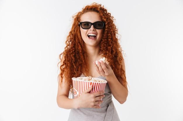 Ritratto di un'attraente giovane donna eccitata con lunghi capelli rossi ricci in piedi isolata, guardando un film e mangiando popcorn
