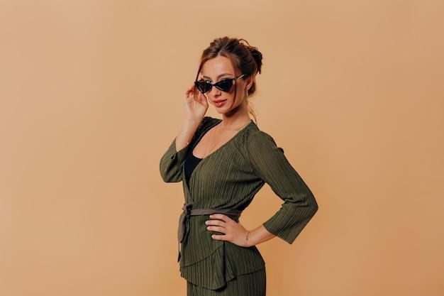 Ritratto di donna alla moda attraente che indossa tuta e occhiali da sole in posa sopra la parete isolata