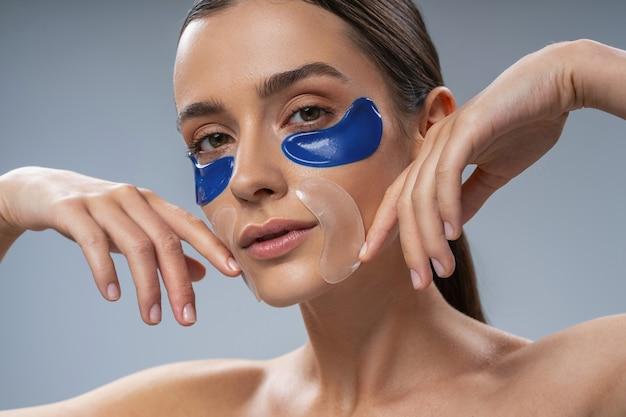 Ritratto di donna attraente che usa i cerotti sotto gli occhi