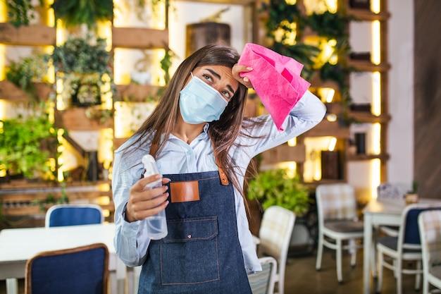 Ritratto di donna attraente cameriera che indossa la maschera per il viso in possesso di una bottiglia con disinfettante e uno straccio in un ristorante. nuovo normale con il concetto di ristorante per l'igiene dell'epidemia di coronavirus.