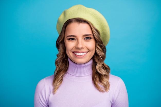 Ritratto di ragazza attraente in berretto verde sulla parete blu