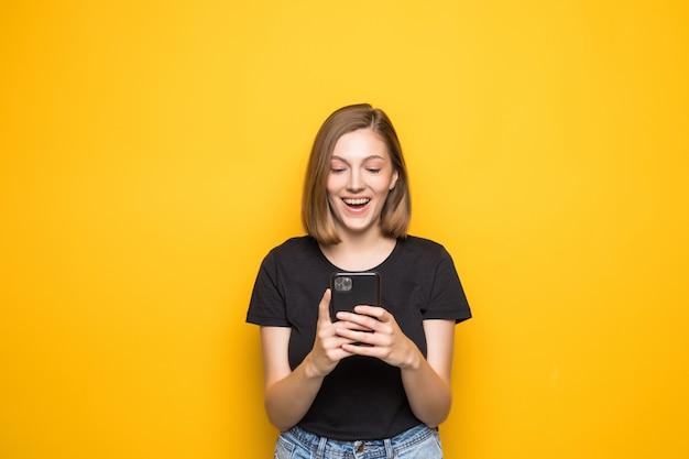 Ritratto di ragazza attraente con smart phone in mano, controllo della posta elettronica, utilizzo di internet 5g, digitazione di sms, in piedi sopra il giallo