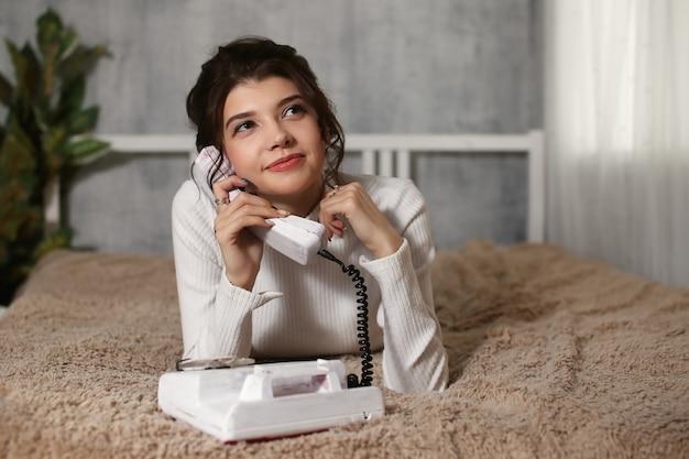 Ritratto di ragazza attraente utilizzando il telefono in mano vicino all'orecchio sdraiato sullo stomaco parlando con l'amante divertendosi