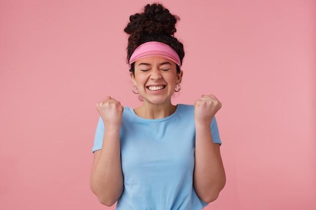 Ritratto di ragazza attraente con chignon di capelli ricci scuri. indossa visiera rosa, orecchini e maglietta blu. ha il trucco. stringi i pugni e socchiude gli occhi per l'eccitazione