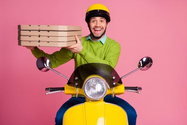 Ritratto di attraente ragazzo felice che trasportano offrendo calda gustosa pizza in sella a una moto