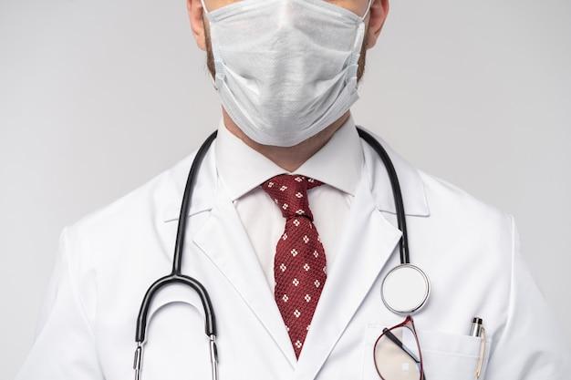 Ritratto di attraente medico bello in maschera protettiva, camice da laboratorio bianco, cravatta isolato sul muro bianco