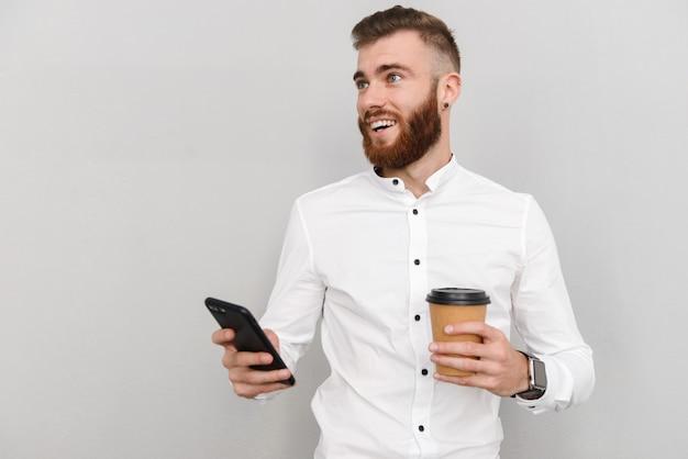 Ritratto di un bel giovane uomo d'affari attraente in piedi su un muro grigio, usando il telefono cellulare mentre beve caffè da asporto