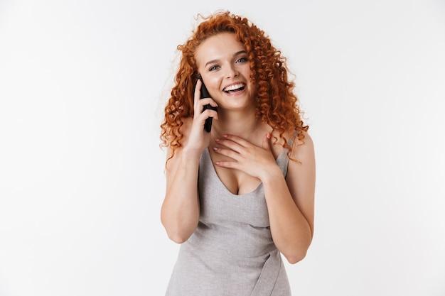 Ritratto di una giovane donna attraente e felice con lunghi capelli rossi ricci in piedi isolata, parlando al cellulare