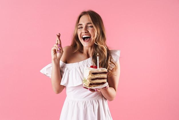 Ritratto di una donna attraente che ride con un abito bianco che tiene le dita incrociate e un pezzo di torta con una candela isolata su un muro rosa
