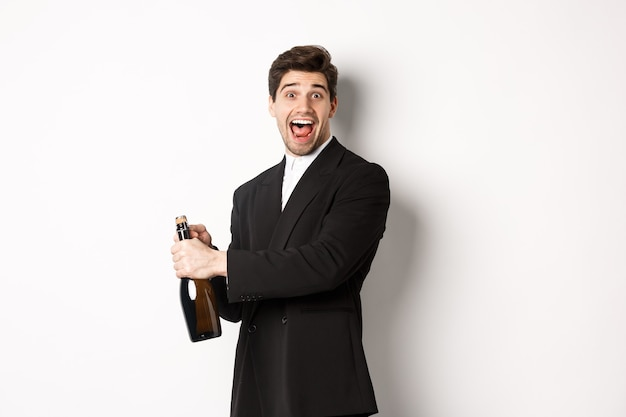 Ritratto di uomo attraente in abito nero, ammiccando alla telecamera e aprendo una bottiglia di champagne