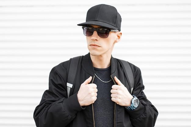 Ritratto di un hipster uomo attraente in un berretto nero in eleganti occhiali da sole neri in una giacca alla moda con uno zaino sportivo sulle spalle su un muro bianco. ragazzo della moda americano.