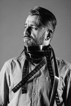 Ritratto di un uomo attraente in una sciarpa da una vecchia pellicola fotografica