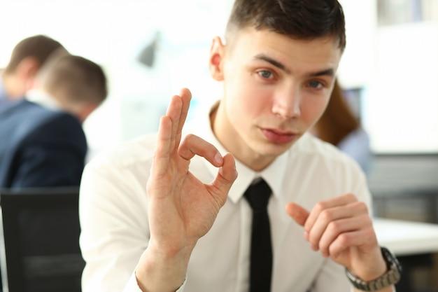 Il ritratto dell'uomo attraente che mostra il segno giusto per lasciare che i buoni colleghi pensino tutto sotto controllo. persone intelligenti che discutono intensamente del progetto commerciale. concetto di incontro aziendale