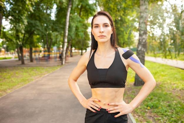 Ritratto di attraente donna bruna muscolare vestita di nero abbigliamento sportivo, guardando la fotocamera. giovane atleta femminile sorridente in posa con le mani sulla vita, kinesiotaping colorato sul corpo.