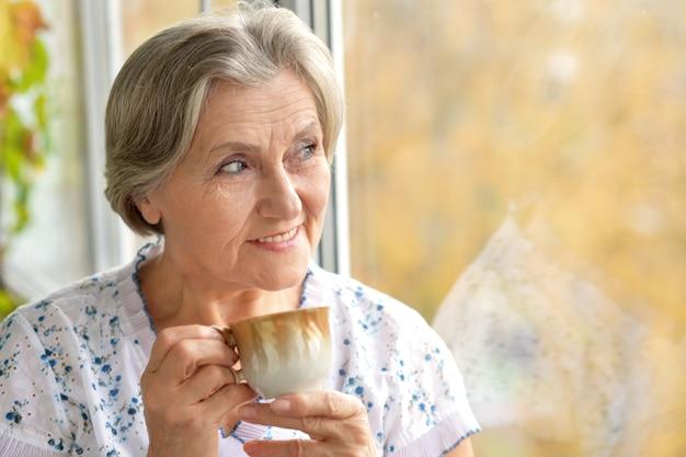 Ritratto di una donna anziana attraente con una tazza di caffè