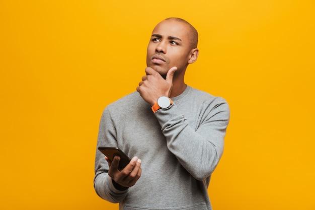 Ritratto di un giovane africano casual pensieroso attraente che sta sopra la parete gialla, tenendo il telefono cellulare