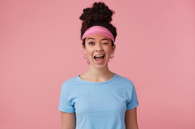 Ritratto di ragazza attraente e giocosa con chignon di capelli ricci scuri. indossa visiera rosa, orecchini e maglietta blu. ha il trucco. concetto di emozione