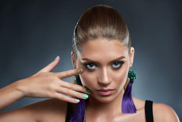 Ritratto di donna attraente e seducente con brillante manicure e trucco nei colori verdi. bella bruna con orecchino viola lungo, viso toccante. concetto di bellezza.