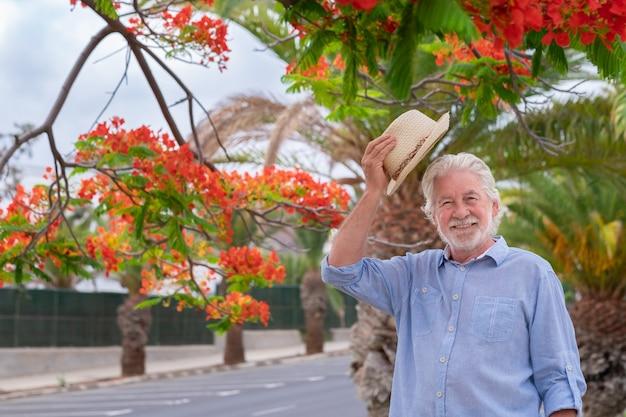 Ritratto di uomo anziano attraente con cappello di paglia in piedi nel parco pubblico godendo della fioritura delle piante. anziani rilassati in pensione