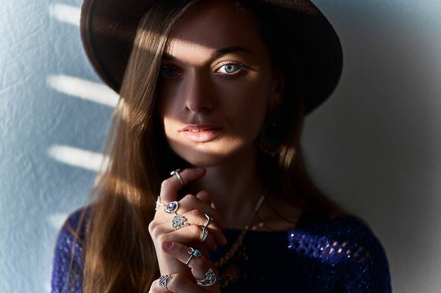 Ritratto della donna castana alla moda sensuale attraente in gioielli d'uso di un cappello con l'ombra delle sovrapposizioni sugli occhi
