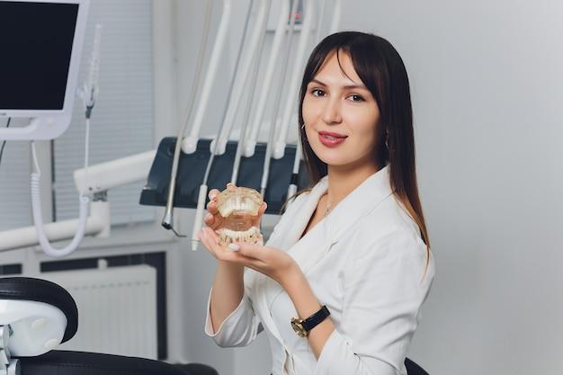 Ritratto del dentista femminile sorridente attraente con le mani piegate.