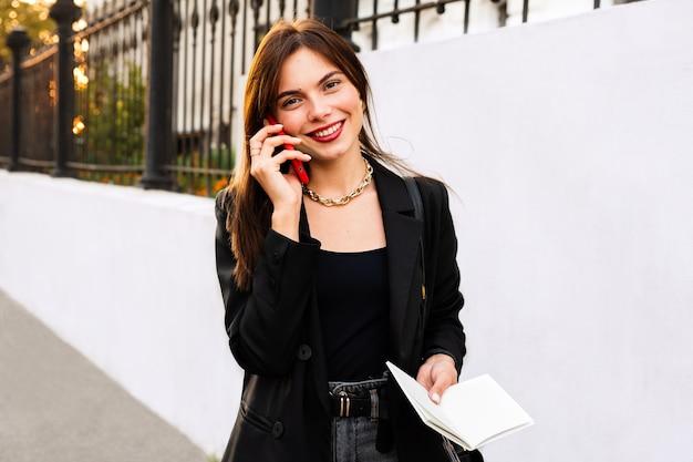 Ritratto di una ragazza sorridente attraente sta parlando al telefono cellulare.