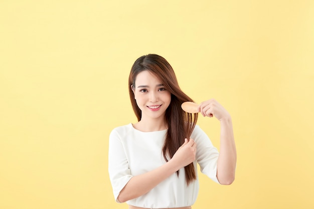 Ritratto di attraente donna sorridente che si spazzola i capelli isolati su giallo studio shot yellow