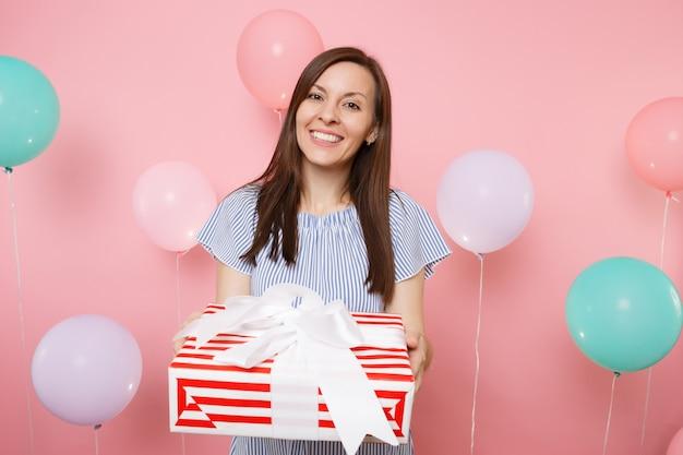 Ritratto di giovane donna sorridente attraente in vestito blu che tiene scatola rossa con regalo presente su sfondo rosa pastello con mongolfiere colorate. festa di compleanno, concetto di emozione sincera della gente.